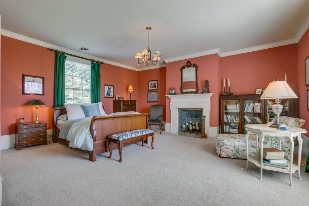Spacious master bedroom with green curtains, an ornate marble fireplace adorned with mirror, fainting couch, and plush white carpeting.