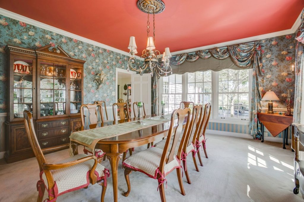 Formal dining room with pink ceiling, Southern-style wallpaper, and ornate furniture.