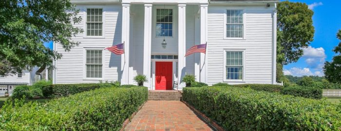 Large two-story Antebellum style home with a red front door, white exterior and columns.