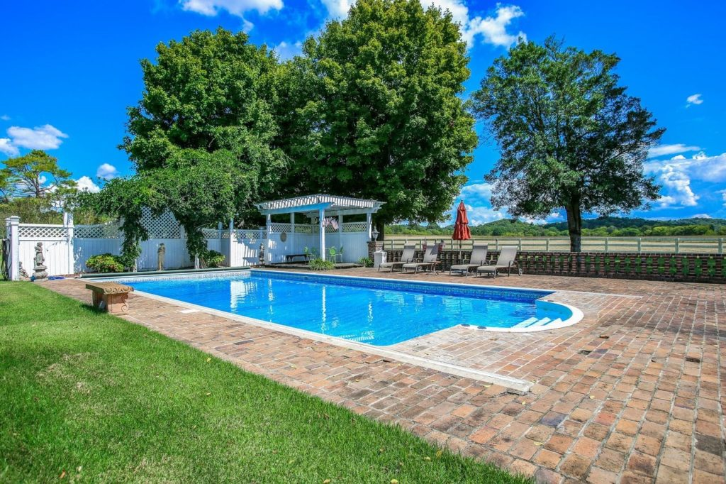 Gorgeous outdoor pool with cobblestone pathway.