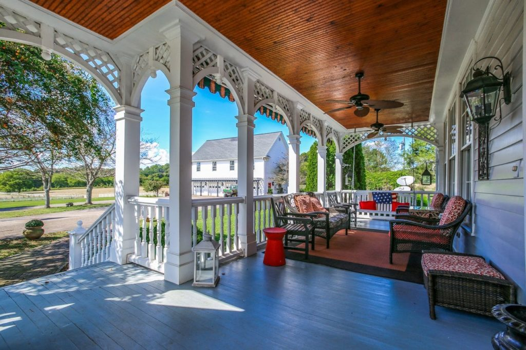 Beautiful covered front porch with white columns and patio furniture.