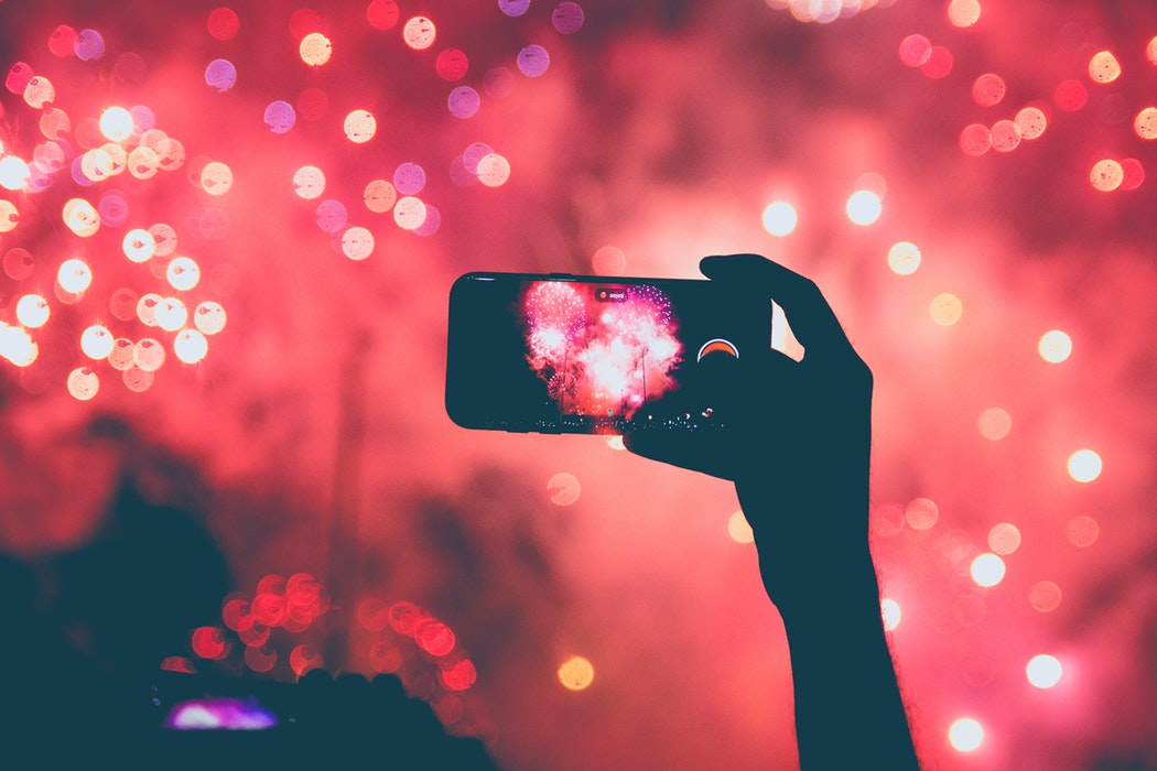 Recording fireworks on a cell phone.